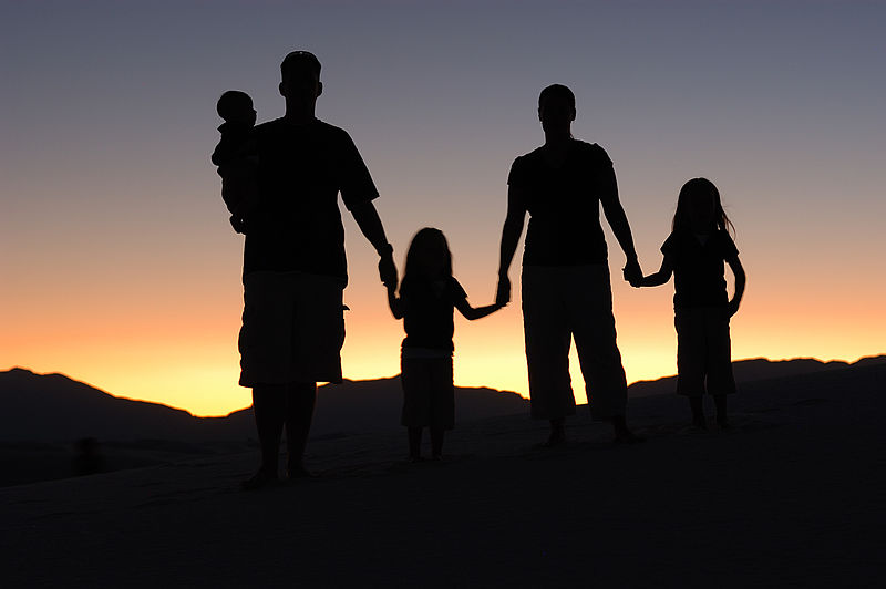 Silhouette of family in sunrise, home for good.