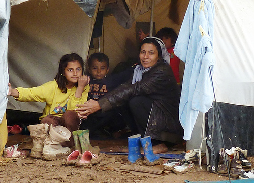 family in Syria sitting on muddy ground